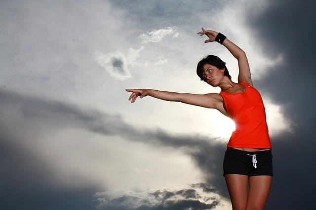 A woman standing in front of a cloudy sky